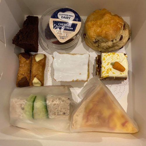 A box containing a delicious Vegetarian Afternoon Tea with sandwiches and cakes at Farmer Copleys