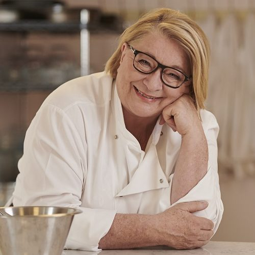 Rosemary Shrager leaning on a table with a metal bowl